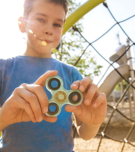 Smiling male student holds up a fidget spinner on a playground
