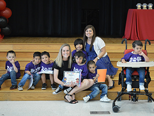 Two happy teachers posing with a class of younger students in purple t-shirts