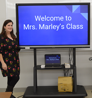 teacher with a TV that says Welcome to Mrs. Marleys class
