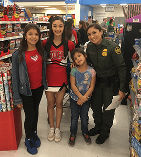 Students pose with a police officer in Walmart