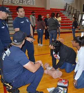 Student learns CPR from emergency staff in the gym
