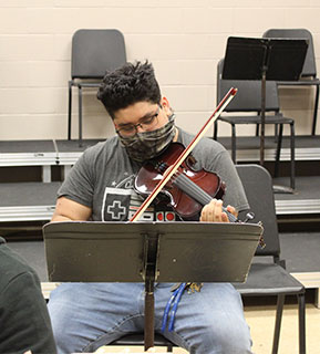 Male student practicing playing violin during class