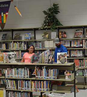Student and teacher walk in a library