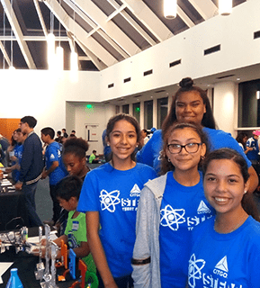 Female STEM students pose with projects