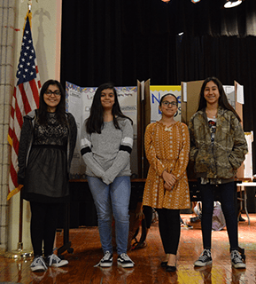 Students pose with projects on stage