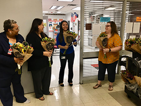 staff members holding flowers