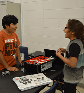 Two students working with tools talk to each other