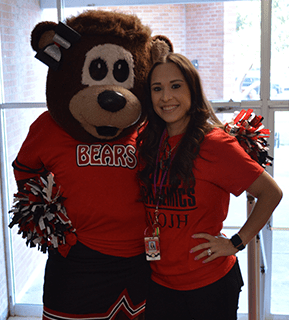 Teacher and a bear mascot wearing a cheerleading outfit pose together