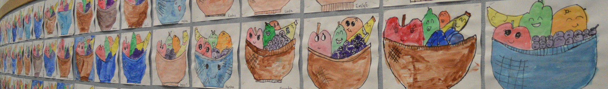 multiple student fruit basket artwork pieces displayed on the bulletin board