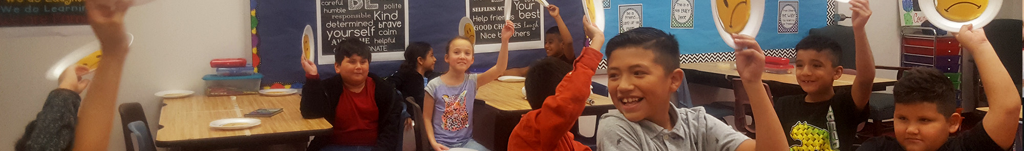 happy elementary students in the classroom with smile plates