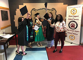 recently graduated student teachers posing in their caps and gowns in the foyer