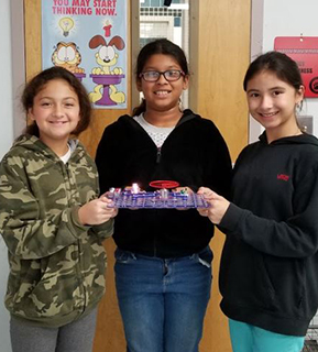 Three happy girls posing with a school project