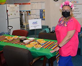 female teacher standing next to donated snacks