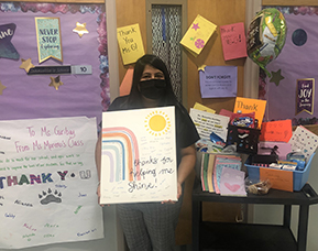 communities-in-school-coordinator-standing with her appreciation sign and gifts