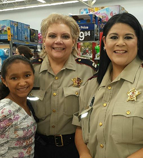 Two women from the Sheriff's office posing for a picture with a female student