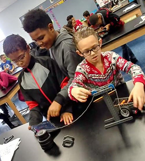 Three students focused on building a robot
