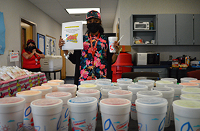 female teacher standing behind a cart of donated sonic drinks