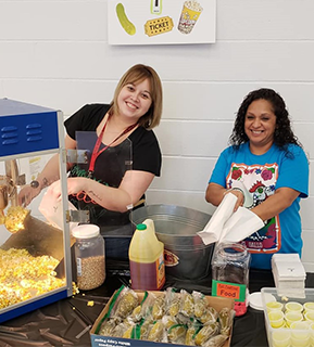 Two staff members running concessions at a school event