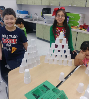 Students with towers built from plastic cups