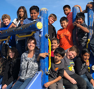 Students and a staff member posing on a playground jungle gym