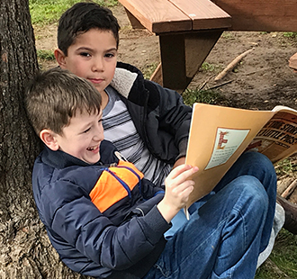 Two students reading together outside