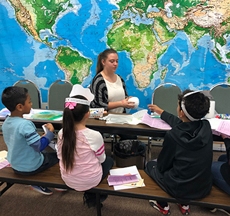 Teacher teaches children in class in front of a world map on a wall