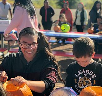Students carving pumpkins outside