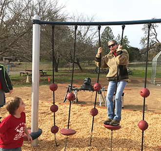 Staff member using a playground jungle gym with a student outside