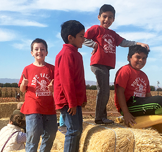 Students posing together on bales of hay outside