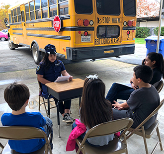 Student sits at a desk outside with other students sitting in chairs in front of a school bus
