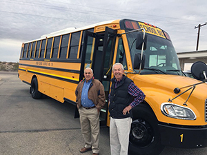 Staff members pose in front of a school bus