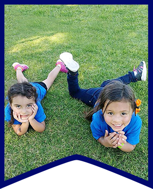 Two students sit on grass