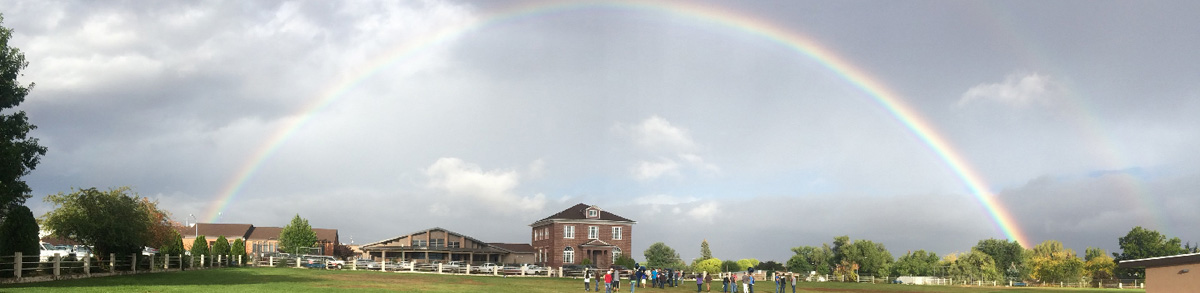 outdoor view of school with double rainbow in sky