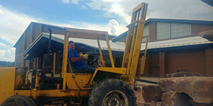 Man operating forklift in front of school