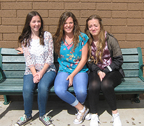 Three female students sitting outside on bench