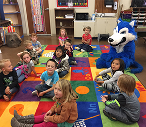 elementary students sitting on class rug with school mascot