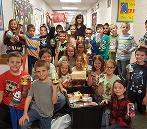 students displaying food drive donations