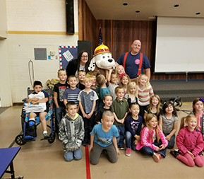 elementary class with firefighter and fire dog mascot