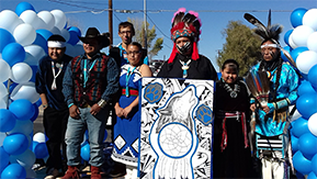 Students dressed in Native American attire pose outside with artwork featuring a wolf, paws and a dreamcatcher