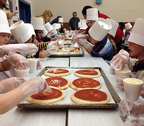students wearing chef hats preparing homemade pizza
