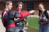 Two male students interviewing a female student