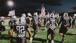 football team running with American flags