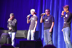 four boys performing on stage