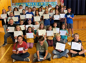 PAWS Winners pose together with their certificates in front of a PAWS Wall of Fame sign