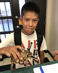 Student Jacobi Mitchell holds turtle found on the playground