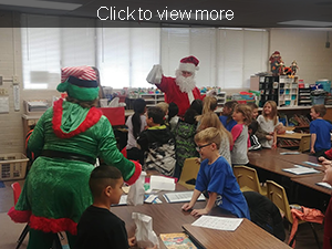 Santa and his helper speak to students in a classroom