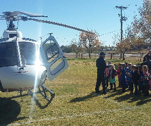 Students stand near a helicopter