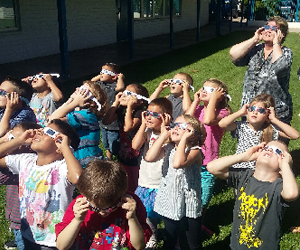 Students wear protective glasses as they look at the sun