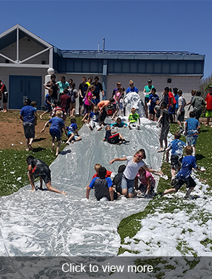 Students sliding down foam slide