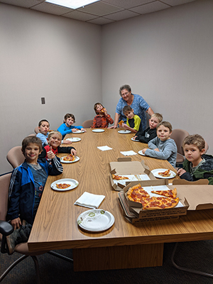 Group of happy students eating pizza with the principal